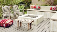 Gray wood deck, concrete firepit, built-in concrete sofa, bright printed pillows
