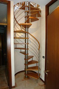 Scala a chiocciola a base tonda, gradini in massello di faggio, barriera in acciaio inox satinato.