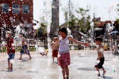 Children play in the Main Street Square fountain on June 26. Temperatures hit a record-breaking 106F