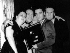 Elvis in april 14 1956 at his new home in Audubon drive in Memphis showing his first gold record for Hearbreak hotel. Here with his father /mother and Dewey Phillips disc jokey in Memphis.