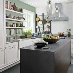 Green walls, pendant lights, soapstone center island, mission style cabinets.