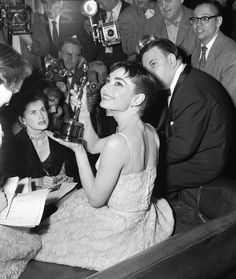 https://flic.kr/p/6fAasT | #39- audrey hepburn | 25 Mar 1954, New York, New York, USA --- Audrey Hepburn, surrounded by photographers and reporters, holds up the Academy Award she won for best actress in , her first American film. ---  Corbis-Bettman