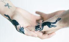 Pareja mostrando sus tatuajes de zorros en las manos