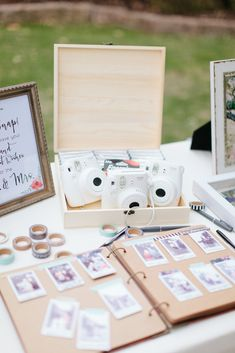 White polaroid cameras sit on a table above a sign-in book where guests have taped photos of themselves and written well wishes // Jen Dillender Photography