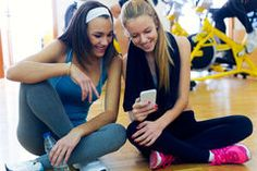 Young women using mobile phone in the gym. Stock Image