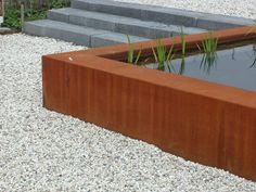 Corten steel raised pond, but with stone on top. Avoid corten contact with water.