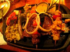 Mama Africa boasts popular meat combos served in generous portions. This is a platter of exotic African animals. African Animals, Cape Town, Homeland, Paella, Bon Appetit, Platter, Exotic, Popular, Meat