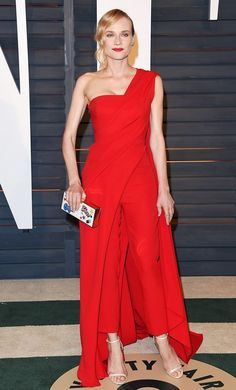 Diane Kruger wears a one-shoulder draped red jumpsuit with white ankle-strap heels and a box clutch