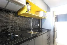 Cozinha pequena colorida! Pastilhas Vidrotil pretas, bancada preta granito são gabriel, nicho em laca amarela, metais Deca Projeto Arquiteta Cristina Gavranic