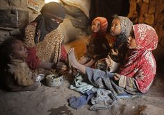 A woman applies traditional Henna dye on the legs of her daughters in their hut in a slum area of the Akhdam community near Sanaa, Yemen. Yemeni Akhdam, or servants, are similar to hereditary castes, but are distinguished by their African features and the menial jobs they perform. (Photo (c) Kaled Abdulla Ali Al Madhi)