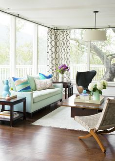 A pastel palette tempers strong leather furniture in a light-filled atrium-like space. | Lonny