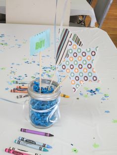Baby Shower Table Centerpieces.    I used mason jars filled with blue Easter grass as the base for the centerpiece. Then I took shaped cut outs and glued them to wood skewers. I tied balloons to the jars and it created a cute centerpiece for the shower.
