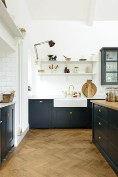 navy cabinets + chevron floor + wall shelves + swing arm light