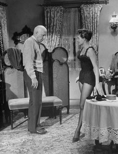 """Director Howard Hawks and his leggy star Angie Dickinson discuss a scene from """"Rio Bravo"""" (1959)."""
