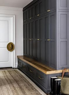 Modern Farmhouse featuring a mudroom with black shaker cabinets and an oak bench accented with brass knobs and pulls.