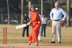 King Philippe of Belgium watched proudly as his wife, clad in a flowing dress and heels, picked up a bat to join in a game