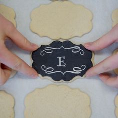 Project by Erica Obrien   Photos by Brooke Allison Photography      The chalkboard look is super trendy right now. This edible version would be great for wedding or shower favors. Be sure to make extras to keep for yourself!      Materials:       Sugar cookie dough     Black fondant     Flour (for rolling dough)      Small acrylic rolling pin     Large acrylic rolling pin     Small palette knife     Letter stencil     Cutter     Royal icing     Baki...