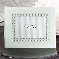 """Elegant frame is made of white frosted glass Features a brilliant double border of clear rhinestones accenting the photo window Central photo window is fit for a 2 7/8"""" x 2"""" photo or place card Easel back swings open for easy insertion of photo or place card Designed for either vertical or horizontal display Packaged in a white box with a """"For You"""" message showing through the window  #timelesstreasure"""