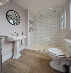 Light purple bathroom walls, white subway tile shower, wood floors. Pretty, romantic bathroom.