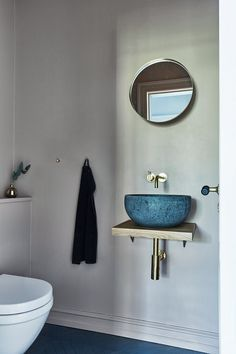 This extra toilet is full of beautiful features such as the brass fixtures and wash-basin that is made from lave stone. The floor is also lava stone and is laid in a herringbone pattern to fit the rest of the house. Scandinavian Home, Beautiful Villas, Vintage House, Interior, Round Mirror Bathroom, House, Stunning Interiors, Wooden Ceilings, Home Decor
