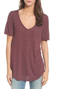 A raw-edged neckline contributes to the relaxed attitude of a drapey tee with a curved shirttail hem.