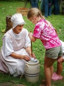 A visit to Historic Cold Spring Village. A young girl churning butter with an interpreter in costume.