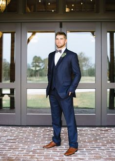 Perfectly fitted blue suit with camel colored shoes and a eucalyptus boutonnière https://www.thecelebrationsociety.com/weddings/modern-greenery-filled-wedding-inspiration-champions-retreat-evans-ga/