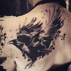 Drawn on the left shoulder-blade, this is a tattoo of a crow landing. The birds' wings are outstretched while its legs are ready to support its weight upon descent. The tattoo is large and has dramatic, artistic blot styling to it.