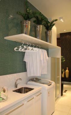 Lavanderia pequena, prática e funcional. As cores harmoniosas tornam o ambiente aconchegante, todos os utensílios ficam armazenados dentro do armário e há espaço para pendurar roupas delicadas ou que foram passadas.