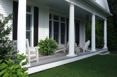 Simple yet elegant, this low-slung porch in Cape Cod, Massachusetts, features classic columns, weathered teak chairs and an ipe floor. The enormous feathery Kimberly Queen fern links the porch to the surrounding lawn.