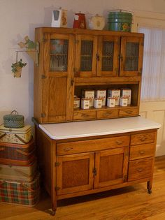 Old Hoosier cabinet -- note wheels -- and bracket under long door - it allows the enameled metal surface to slide out when needed and back in to conserve space.