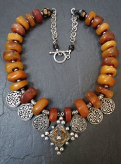 by Luda Hunter | Genuine antique Moroccan natural amber beads are combined with an enamelled Berber cross pendant from Tiznit (Morocco) and six Berber silver charms. The last two beads are antique Venetian King Bicone beads dating from the late 1850s - 1920s | Sold