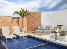 A piscina tem pastilhas no tom azul marinho, que contrastam com os tijolos da parede e o granito cinza das bordas (Foto: Divulgação)