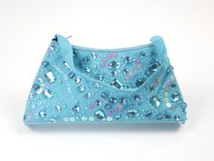 "Amanda Beaded and Sequined Sea Blue Bag. The front of this bag is covered in large and small beads and sequins. The top and bottom are edged with a row of tiny beads. The handle matches the fabric of the purse. It measures 12.5"" wide, 2"" deep and 5.5"" high."