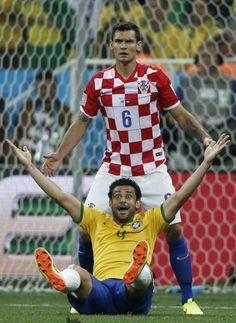 Brazil's forward Fred (front) is fouled by Croatia's defender Dejan Lovren to be awarded a penalty during a Group A football match between Brazil and Croatia at the Corinthians Arena in Sao Paulo during the 2014 FIFA World Cup on June 12, 2014.
