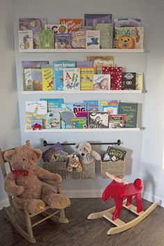 Great reading area in a nursery - love the library wall and hanging baskets for extra storage!