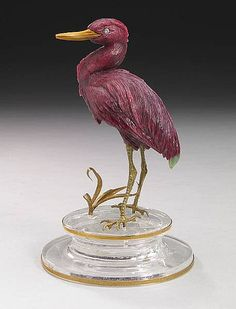 By Eberhard Bank Idar-Oberstein, Germany Rich red ruby-in-zoisite from Tanzania has been used in this elegant carving depicting a heron amidst marsh grasses. The green zoisite has been imaginatively positioned to depict his tail feathers. The eyes are set with diamonds and the beak is fashioned of jasper, with gold vermeil legs. Raised on a circular rock crystal base, rimmed in 18K yellow gold. Height 5in