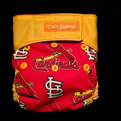Major League Baseball Cardinals spirit! This is a made to order AI2 (All In 2) cloth diaper with a prewashed 100% organic fiber soaker of buttery soft bamboo fleece (2 layers) and hemp fleece (2 layers) included. The shell is made with Waterproof PUL that is sandwiched between high quality cotton fabric and a super soft suedecloth inner liner.  Snapped front for sizing. Large elastic back. Contoured PUL leg gussets, adjustable velcro style closures with fold over tabs for easy washing. The…