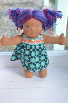 "This is Lyrica, a Bamboletta Little Buddy from the January 11, 2013 upload. She has dark tan skin, hair made with wool and mohair yarns in multi-tonal blue and purple colors and blue eyes. She is wearing the pictured outfit and underpants.    These dolls measure approximately 10"" in height.  They are hand made with wool, cotton, and lots of love by team Bamboletta in Canada."