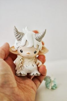 There are two newborn fauns at Mijbil Creatures, and the WHITE one is for sale here (turquoise faun available in a separate listing).  This little gy has been handsculpted from a Kidrobot Micro Munny, baked several times and painted with 5-6 layers of high quality acrylics. He has a tiny silver...