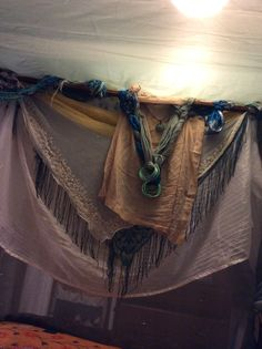 Inside the bed. Front. Vintage Scarves from my own collection and thrifting, Bangles from India. attached to canopy frame. The bed was built in 1800's, The frame is fragile but I used thumb tacks to attach fabric to the top and sides.