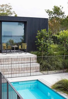 Exterior: Landscaping by William Dangar of Dangar Barin Smith pops against the dark New Guinea rosewood exterior, which was given a Resene Woodsman timber stain in Crowshead. Harp 359 Armchair by Roda with Smoke frame and olive cord, Robert Plumb.