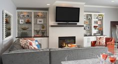 living rooms - Kelly Wearstler Imperial Trellis - Charcoal lined built-ins flanking modern fireplace TV gray velvet sectional sofa orange chair nailhead trim orange pillow gray walls