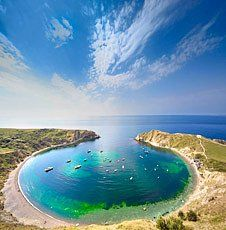 Lulworth cove, England. Known for its unique shape and beautiful views.