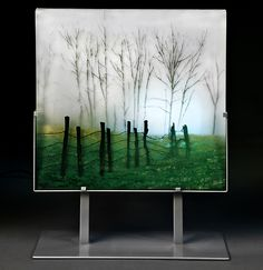 """This kiln-worked glass panel is hand painted, using enamel, on individual layers of glass. When all the layers are complete, they are stacked in a kiln and fused into a solid panel. Multiple layers gives the work incredible depth and dimension. This panel is made from 9 layers of glass, and is over 1"""" thick. It is displayed in a metal gallery stand, which is included with your purchase. Dimensions listed include the base."""