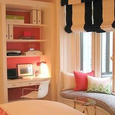 Fabulous girl's room features stacked floating shelves over floating desk filling nook next to kidney shaped window seat adorned situated under windows dressed in black and white striped roman shades.