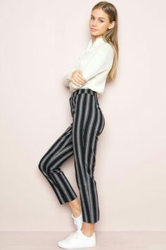 a1a795c4f5 High-rise trouser pants in black and white stripes with a button and zipper  front, elasticized waistband and a slit on the back hem.