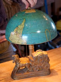 The world is dissected at the equator then the Southern Hemisphere is turned upside down to create a semicircular lampshade.