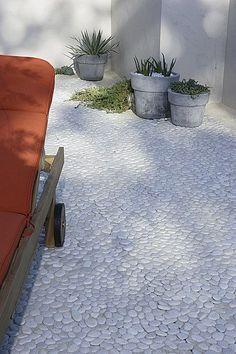 Pour une terrasse en galets, des dalles de 30 x 30 cm qui s'emboîtent les unes aux autres. Pose sur dalle de béton. Non carrossable. Existe aussi en noir. Cimiez. Leroy Merlin.