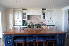 Brick backsplash with soft white cabinetry, striking blue island....